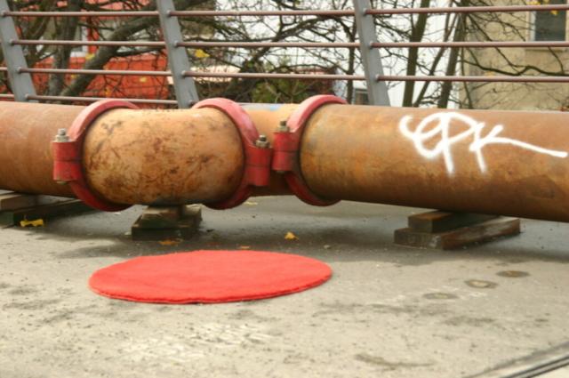 Roter runder  Teppich neben einem senkrechten Rohr
