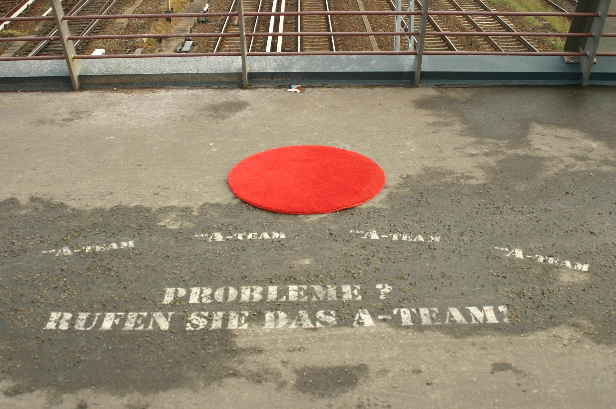 Roter runder Teppich auf der Straße: Probleme? Rufen sie das A-Team