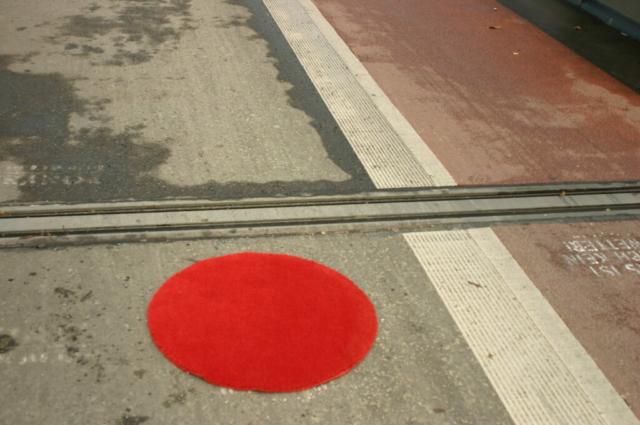 Roter runder Teppich neben einem rot markierten Fahrradstreifen